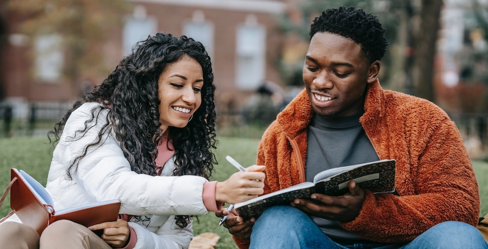 Two students sitting in a college quad studying personal finance together