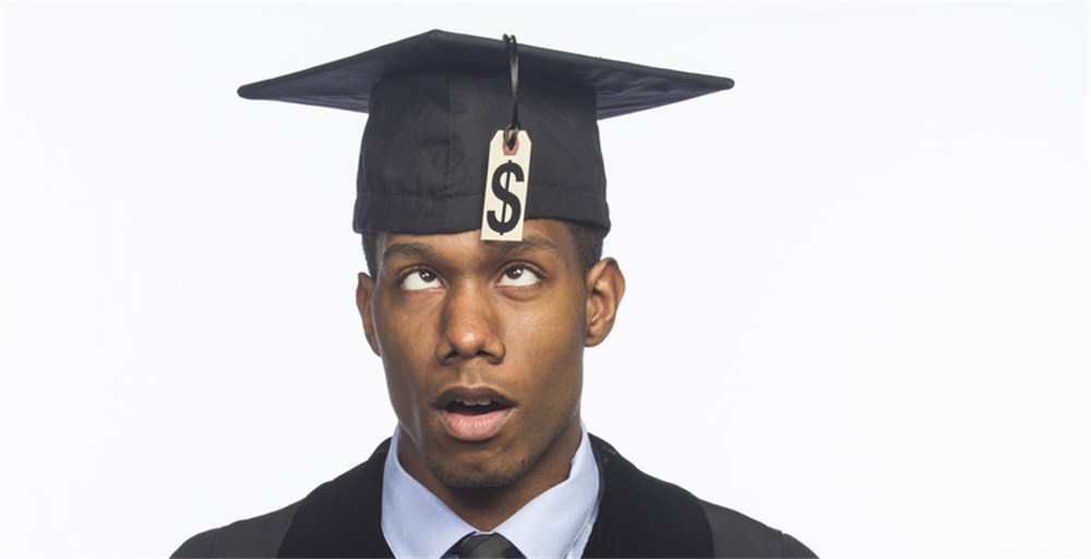 Man wearing graduation cap that has dollar sign as a tassle