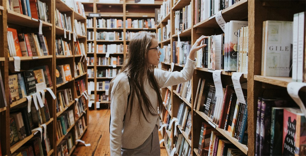 woman in college library looking at books