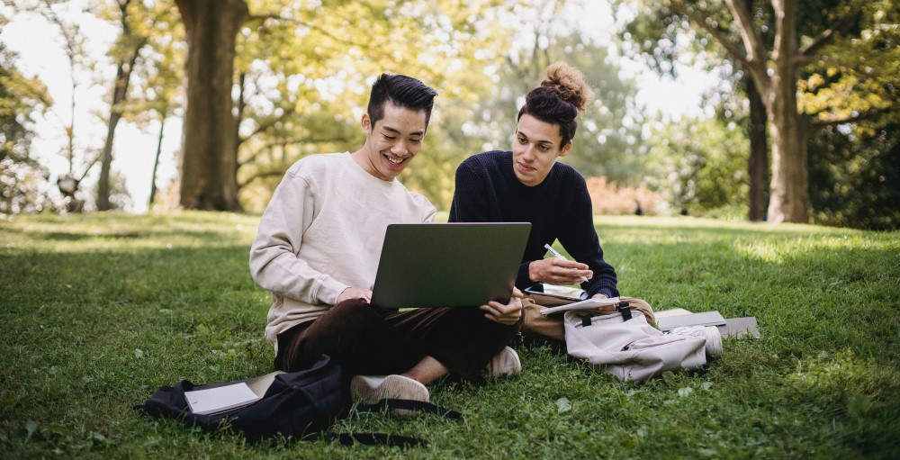 Two college students sitting in grass studying together