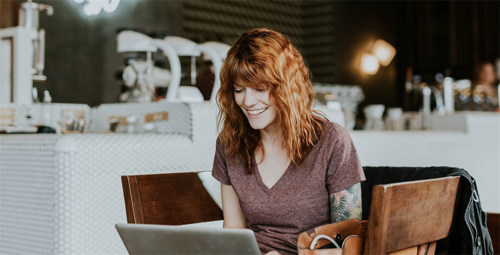 Female employee with red hair smiling and working on a laptop