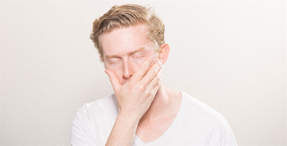 employee suffering from financial stress covering face on white background