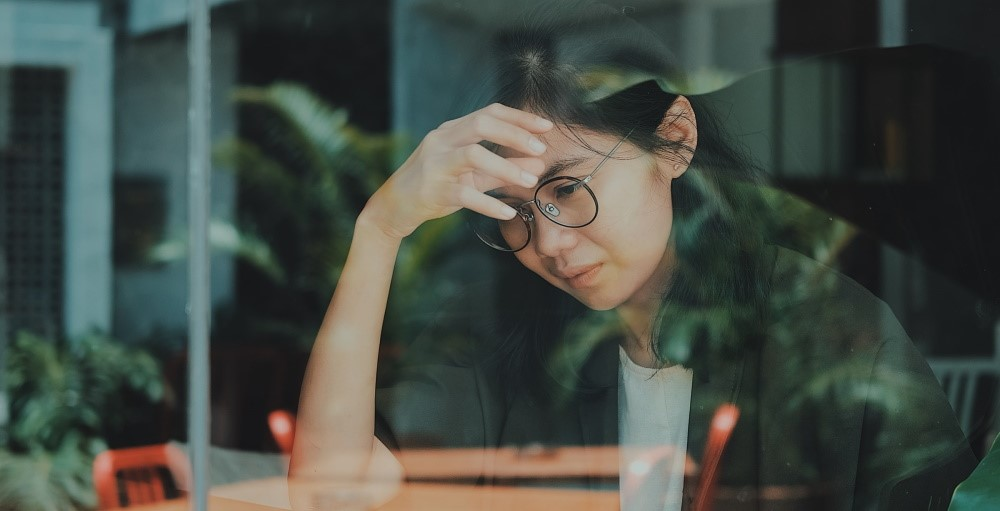 Woman in a coffee shop stressed about her finances looking out a window