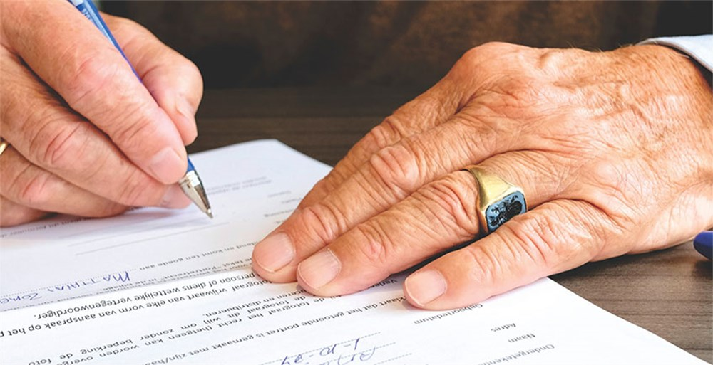 Elderly man's hands signing a financial contract