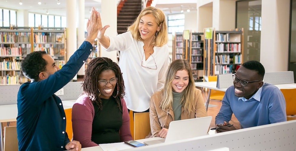 College students gathered in a library at a desk learning how they can decrease the amount of student loans they borrow to pay for a semester of school