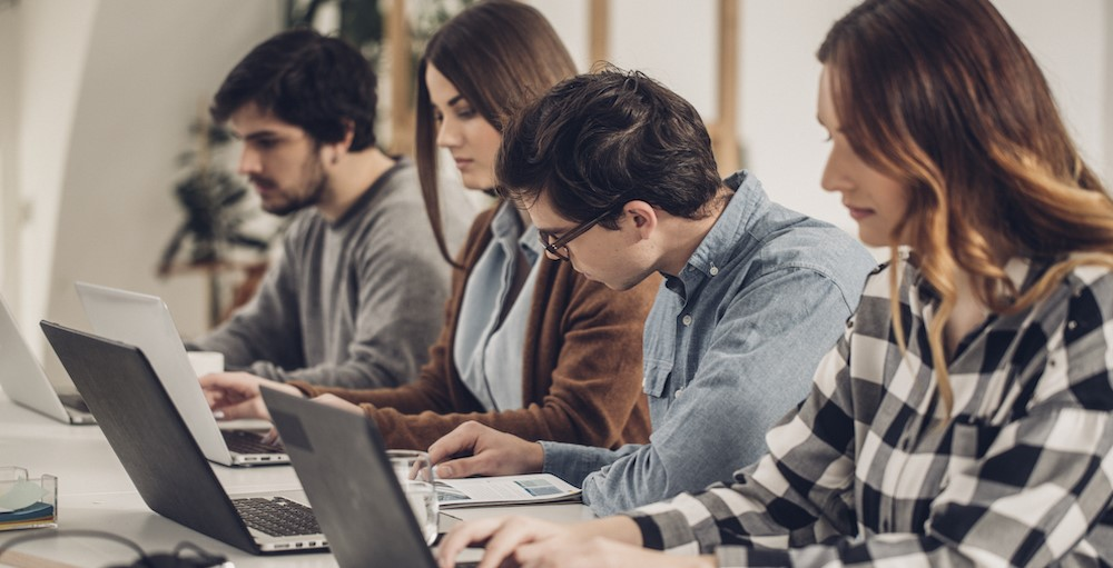 College students taking financial education courses on the iGrad platform on their computers