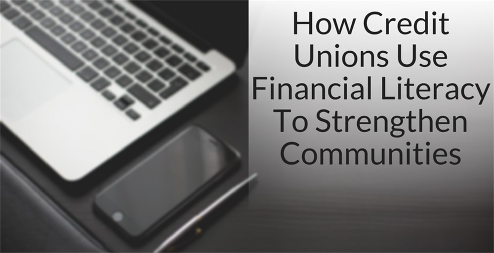 "Black styled desk with phone, computer and pen stating ""How Credit Unions Use Financial Literacy To Strengthen Communities"""