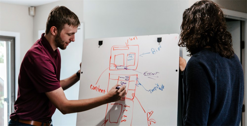 two people drawing on a dry-erase board