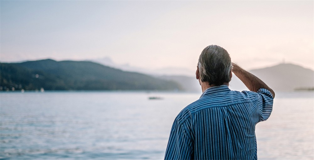 retired man in striped shirt looking out at a lake