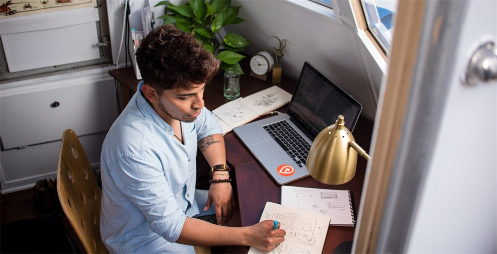 Remote employee working from home office in blue shirt writing at desk in front of Macbook Pro
