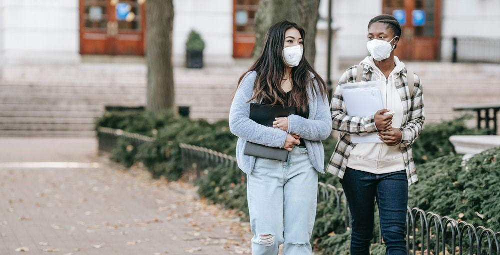 Two women students with masks walking through a college campus
