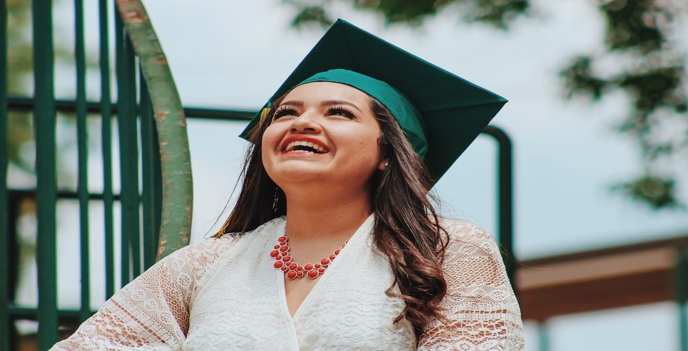 Woman at college graduation smiling wearing cap