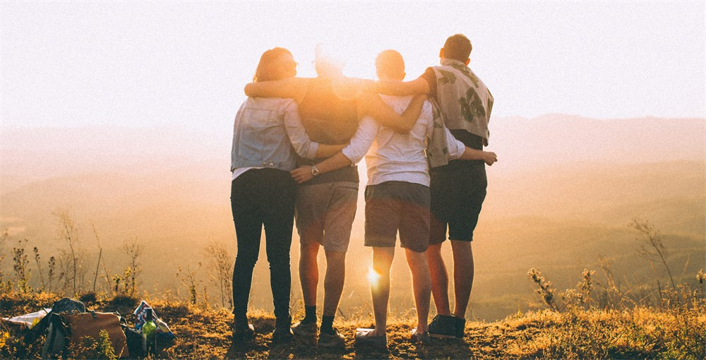 four college students with hands wrapped around shoulders while looking at sunset