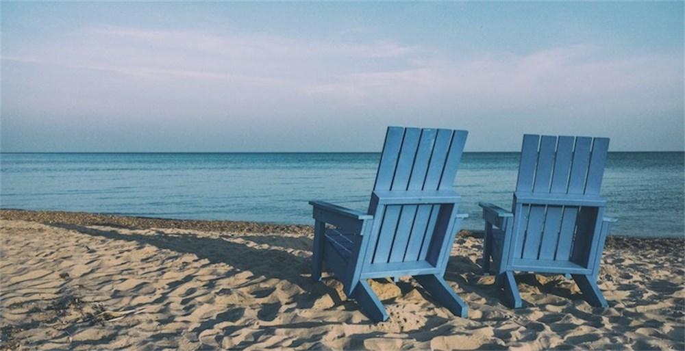 two-wooden-chairs-on-beach-facing-ocean