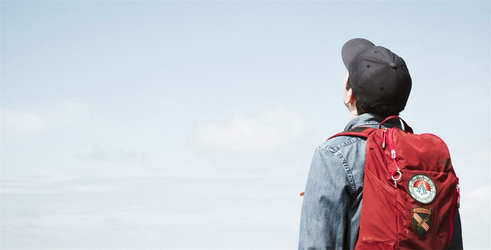 college student with red backpack and black hat looking at sky