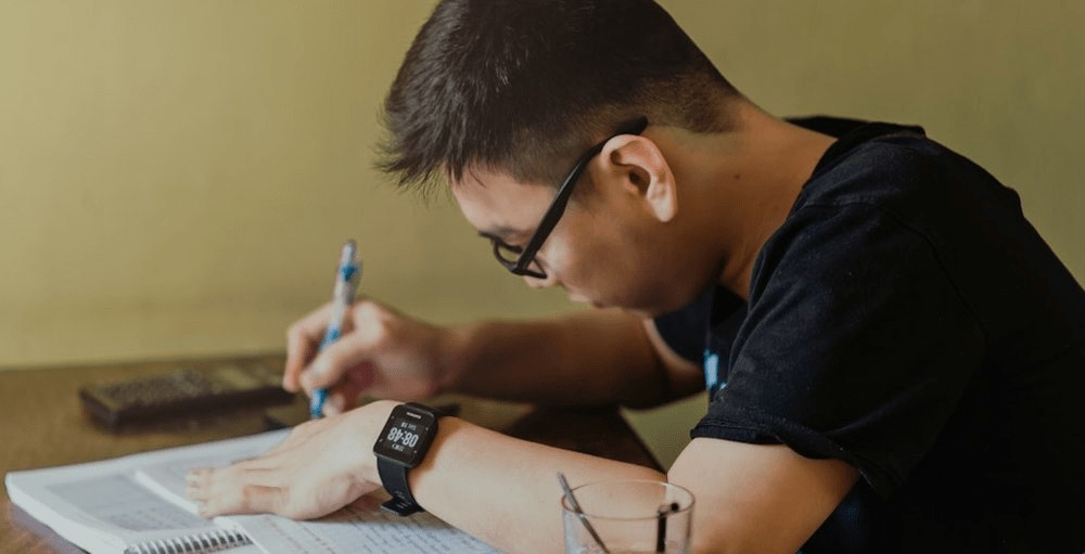 A male college student studies for his personal finance test at a desk